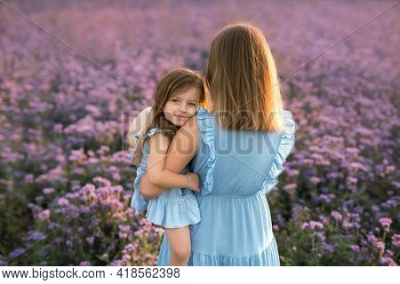 Little Girl In A Field Of Purple Flowers Hugs Her Mother Tenderly. Mom Holds Her Daughter Tightly In