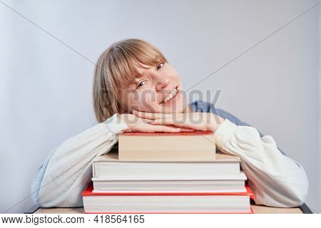 Attractive Blonde Student Or School Girl Relaxing Lying On Stack Of Books And Smiling. Young Female