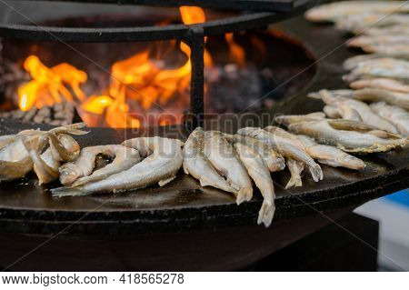 Process Of Cooking European Smelt Fish On Black Brazier With Hot Flame At Summer Outdoor Food Market