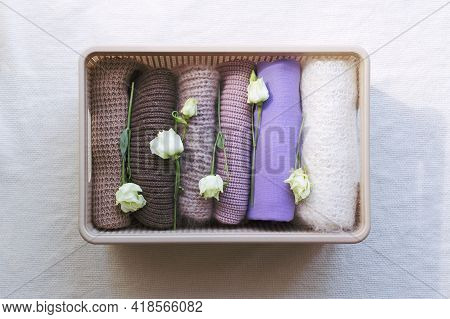 Warm Knitted Clothes In Brown And Purple Shades Are Neatly Folded In A Wicker Box And Decorated With