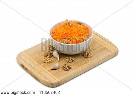 Grated Carrots And Walnuts In A White Bowl, Next To Garlic Cloves