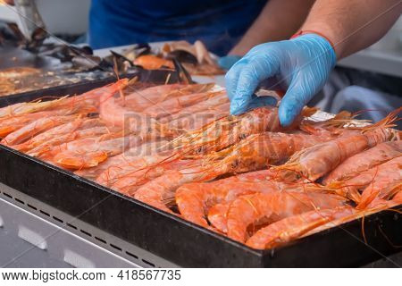 Chef Cooking Fresh Red Langoustine Shrimps, Prawns On Grill At Summer Local Food Market - Close Up.