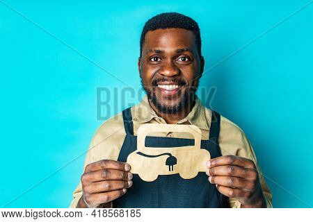 Mixed Race Man Holding Paper Car With Recharging Socket In Blue Studio Background Eco Electro Car Co