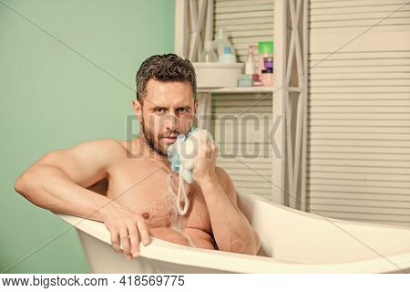 Macho Sitting Naked In Bathtub Washing With Sponge. Hygiene And Health. Sexuality And Relaxation. De