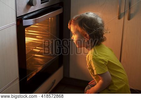 A Child Is Sitting Near The Oven In The Kitchen And Waiting. Curious Boy Is Watching Through The Gla