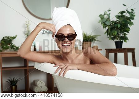 Lovely Girl With Vitiligo Smiles A Snow-white Smile And Sits In The Bathroom. Stylish Woman In Towel