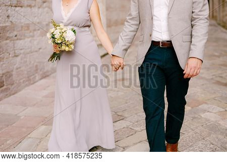 Groom Holds The Hand Of Bride In A Wedding Dress With A Bouquet Of Flowers. Newlyweds Stroll Along A