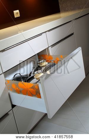 Drawer with pots in modern kitchen