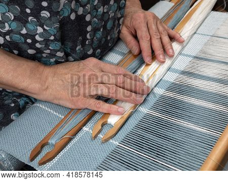 Weaver's Hands With Two Shuttles Are Lying On A Handloom. Hand-weaving Of A Striped Fabric. Concept