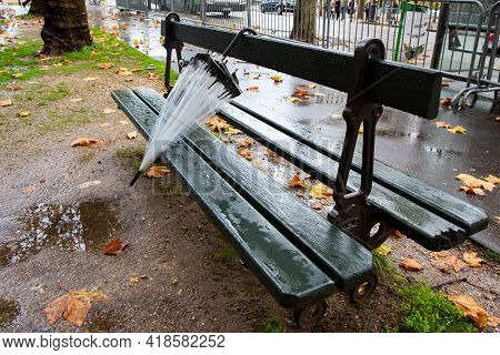 Paris, France, 1.11.2019 - Transparent Umbrella Forgotten On Green Street Bench In Champs Elysees On