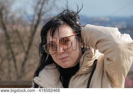 Portrait Of A Beautiful Middle-aged European Woman With Wrinkles, Dark-haired, In Glasses Against Th