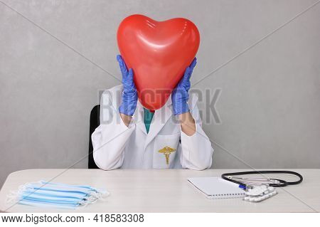 The Doctor Holds On To A Heart-shaped Balloon Imitating His Head. Cardiologist. The Doctor Holds His