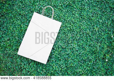 Paper Bag On Green Grass And Small Tree. Flat Lay Or Top View With Copy Space. Shopping And Saving