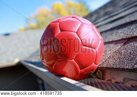 Red soccer ball stuck on gutter mesh on a roof