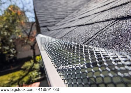 Plastic guard over gutter on a roof