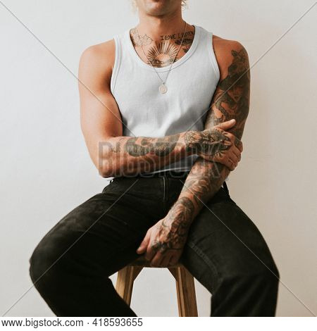 Handsome man in white tank top and black pants studio shot