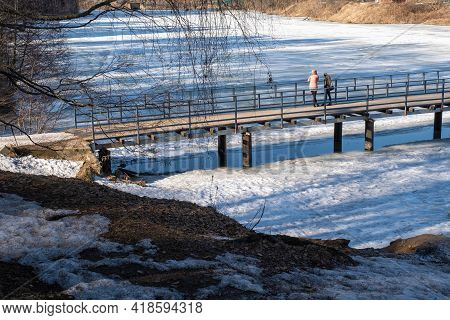 Pedestrian Bridge Over The River In The Low Rays Of The Spring Sun, Russia.