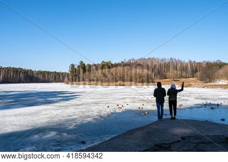 Two Young Men Feed Ducks On The Bank Of An Ice-covered River On A Sunny, Cloudless Day.