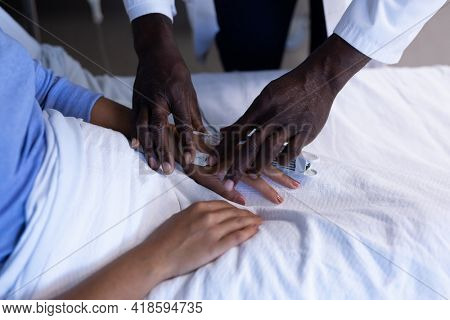 Midsection of african american male doctor putting oximeter on finger of patient in hospital bed. medicine, health and healthcare services.