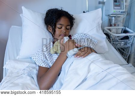 Mixed race sick girl asleep in hospital bed wearing fingertip pulse oximeter and holding teddy bear. medicine, health and healthcare services.