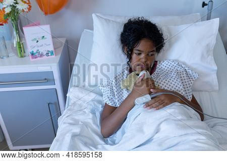 Mixed race sick girl sitting up in hospital bed wearing fingertip pulse oximeter and holding teddy. medicine, health and healthcare services.