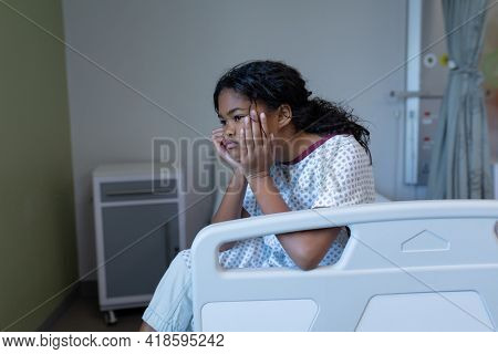 Bored sick mixed race girl sitting on bed in hospital ward holding head in hands. medicine, health and healthcare services.