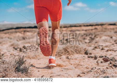 Runner sprinting running away rear view closeup of red shoes. Training triathlon athlete on trail run outdoor exercise endurance workout.