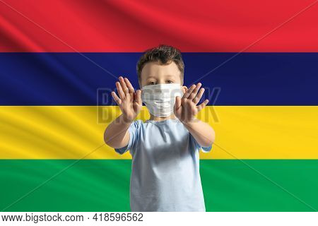 Little White Boy In A Protective Mask On The Background Of The Flag Of Mauritius. Makes A Stop Sign