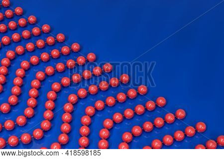 Background From Red Plastic Beads On A Transparent Fishing Line. The Beads Are Arranged Diagonally.
