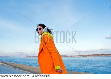 Good-looking Young Woman Walks Outside On Pier Next To Sea. Real People. Hipster Girl Listens To Mus