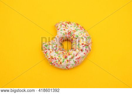 Donut With Colorful Sprinkles On Yellow Background. Pink Frosted Donut With Colorful Sprinkles