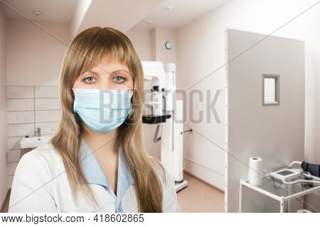 Female doctor mammologist or radiologist working in the room with equipment for breast x-ray
