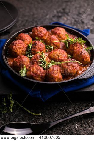 Meat Balls With Tomato Sauce  In A Frying Pan On A Black Background.meat Balls With Tomato Sauce  In