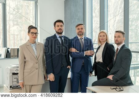 Team of confident lawyers in suits standing together in office and looking at camera