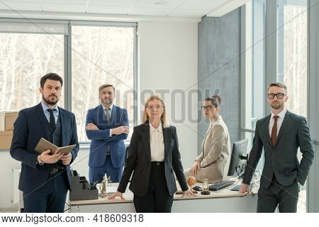 Portrait of serious confident business colleagues in formalwear posing at office table and preparing for meeting