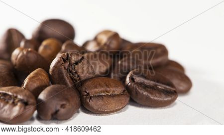 Black Coffee Beans On A White Background. Close-up Of Roasted Coffee Beans Heap Isolated On White. A
