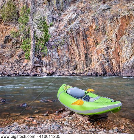 inflatable whitewater kayak with a paddle - Poudre River above Fort Collins, Colorado, in early spring