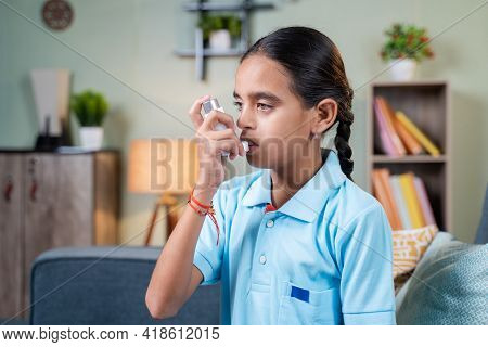 Side View Young Girl Kid Using Asthma Medication Inhaler After Taking Deep Breath - Concept Of Asthm