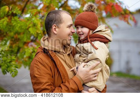 Portrait Of Happy Father And Little Daughter In Autumn Park