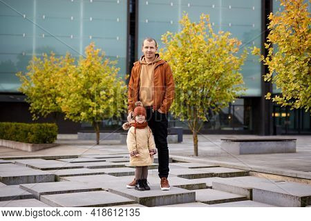 Family And Happiness Concept - Happy Father And His Little Daughter Posing In Modern Autumn Park