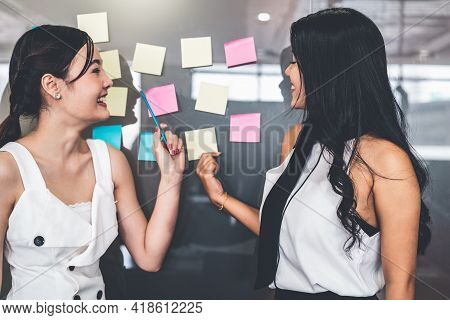 Two Young Beautiful Asian Businesswomen Talk And Discuss Creative Post On The Window. It Is Project