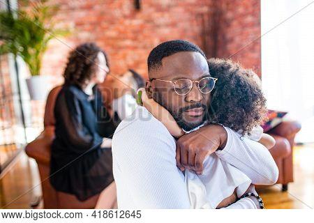Portrait Of Upset Man Hugs His Cute Curly Baby Girl In Living Room