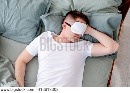 Young man sleeping in the bed wearing white t-shirt and eye mask. Guy lying on his back and napping in the room with sunlight in the morning. Concept of resting time