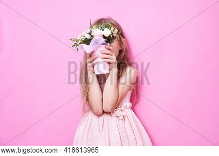 A Little Girl In Pink Dress With Bouquet Of Flowers In A Paper Cup, Hid Behind The Flowers. The Girl