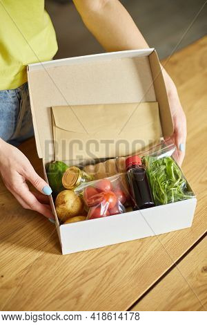 Woman Put On The Table Food Box Meal Kit Of Fresh Ingredients Order From A Meal Kit Company