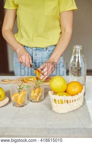 Female Hand Cut Orange, Woman Preparing, Making Citrus And Rosemary Fresh Lemonade
