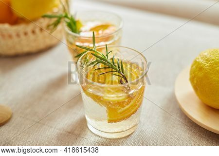 Citrus And Rosemary Fresh Lemonade In Glass On A White Table At Home
