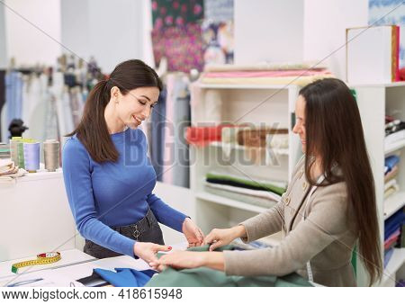 Woman Assistant In Fabrics Shop Demonstrating Khaki Color Textile To Young Tailor Girl Customer. Int