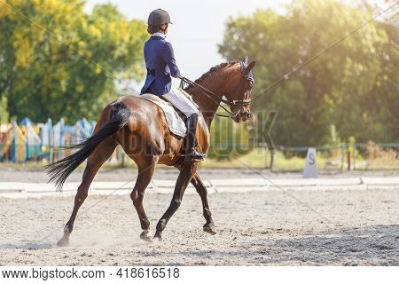 Young Girl Riding Horse At Dressage Advanced Test