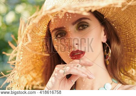 Close up portrait of a romantic brunette girl with make-up in straw hat outdoor. Beauty and make-up.